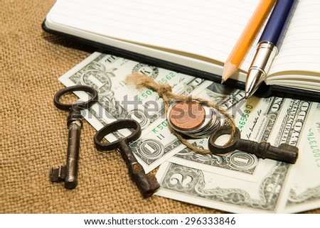 Opened notebook with a blank sheet, pen, pencil,  key and money on the old tissue - stock photo