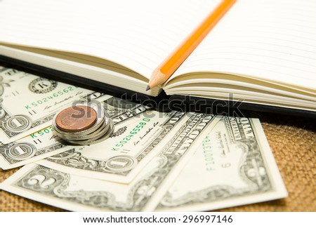 Opened notebook with a blank sheet, pencil and money on the old tissue - stock photo