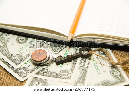 Opened notebook with a blank sheet, pencil, key and money on the old tissue - stock photo