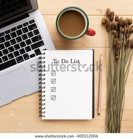 Opened notebook with to do list and cup of fresh coffee on desk - stock photo