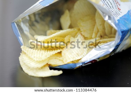 Opened pack of delicious spicy potato chips over black  table. Open bag with potato chips. Potato chips in bag on reflecting background.  - stock photo