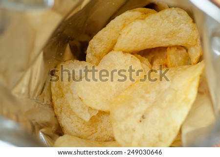 Opened pack of delicious spicy potato chips view inside of pack macro with shallow depth of field - stock photo
