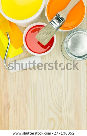 opened paint cans, brush, roller and color samples on wooden background - stock photo