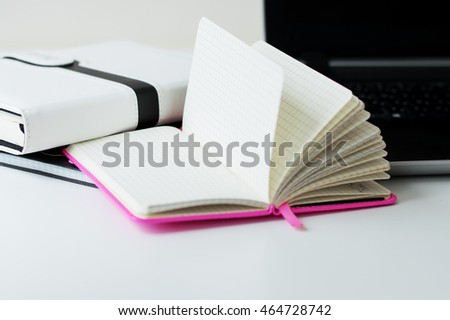 Opened paper notebook with blank sheets on white office table, laptop and book as background