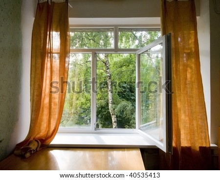 Opened plastic window in room with view to green trees