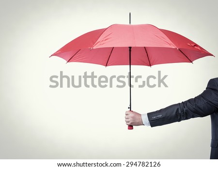 Opened red umbrella in hand, toned photo.
