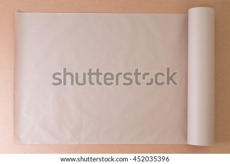 Opened roll of plain brown paper on cardboard for creative artistic designs or craft work, overhead view with copy space - stock photo