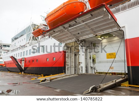 opened side ramp gate on big passenger ferry in port - stock photo