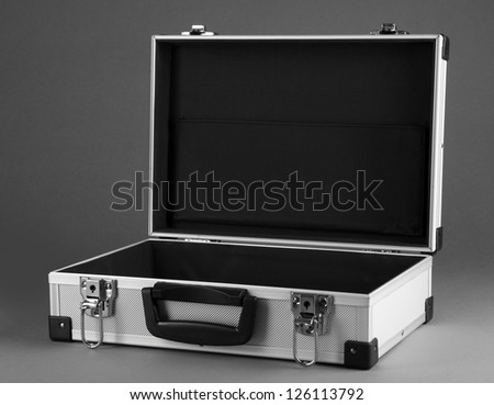 Opened silvery suitcase on grey background