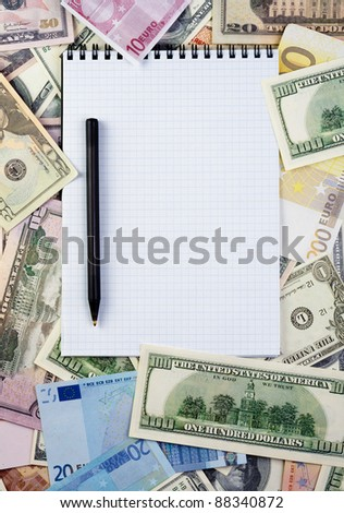 Opened spiral notepad (notebook) sheet in a cage on money background ( euro and dollars cash).   with black pen