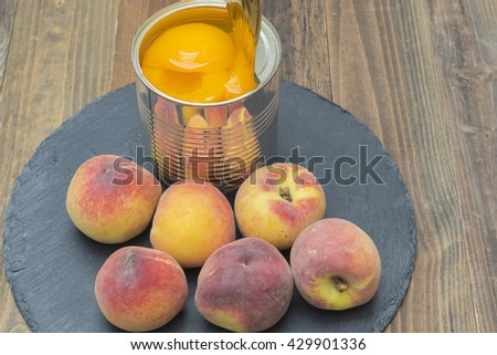 Opened tin can with preserved peaches, fresh peaches around the can - stock photo