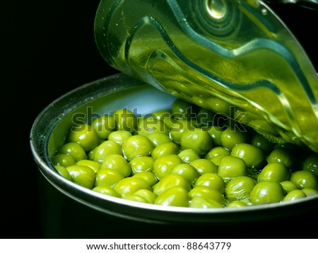 Opened tin with green peas. Isolated on black. - stock photo