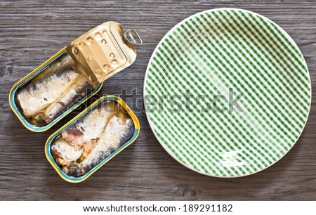 Opened tins of sardines with a green plate - stock photo