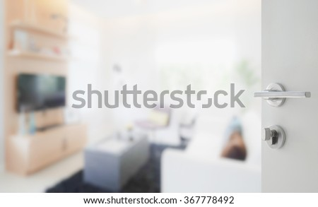 opened white door to modern living room interior - stock photo
