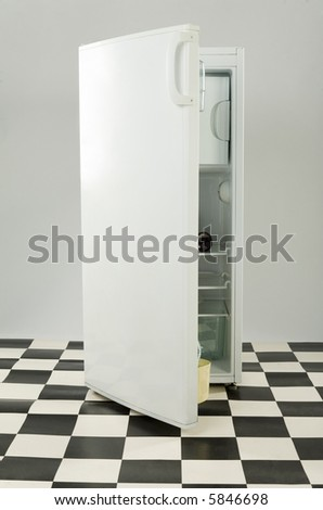 Opened white fridge on black and white floor. Front view. - stock photo