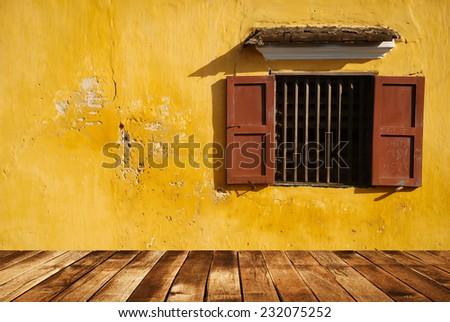 Opened window on yellow wall and wood floor - stock photo