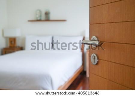 opened wooden door with blurred bedroom - stock photo
