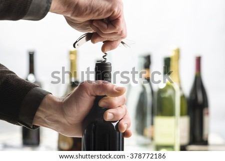 Opening bottle of wine with corkscrew - stock photo
