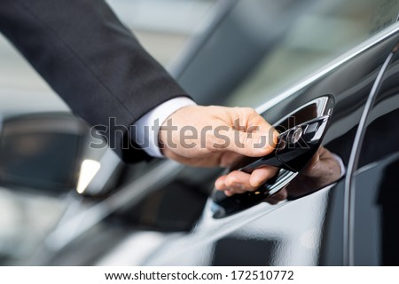 Opening his new car. Close-up of male hand holding the car handle - stock photo