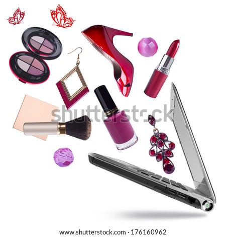 Opening laptop pc with cosmetic products flying out on white - stock photo