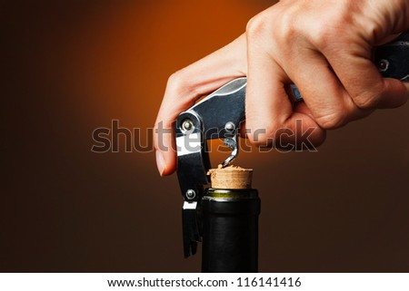 Opening of bottle of wine with corkscrew - stock photo