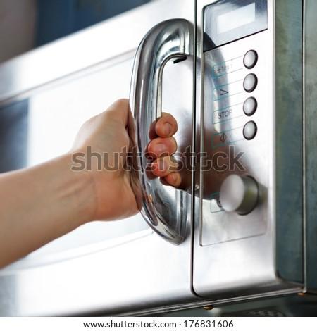opening of microwave oven door in home kitchen - stock photo