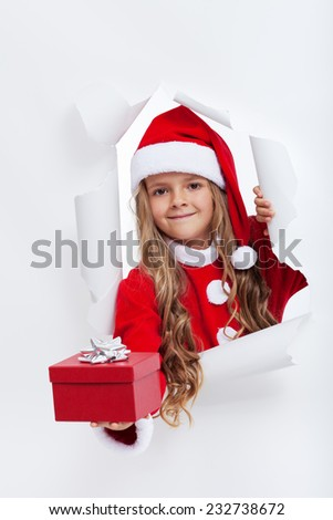 Opening the holidays season - little girl in santa costume offering you a present - stock photo