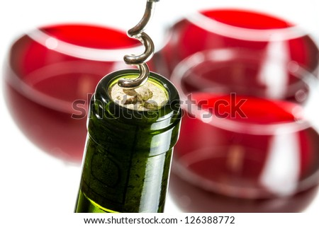 Opening wine bottle on red glass background - stock photo