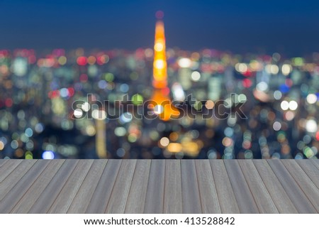Opening wooden floor, abstract blurred bokeh Tokyo cityscape aerial view, night light - stock photo
