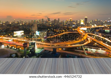Opening wooden floor, Aerial view burred light city interchanged road and office building background during sunset - stock photo