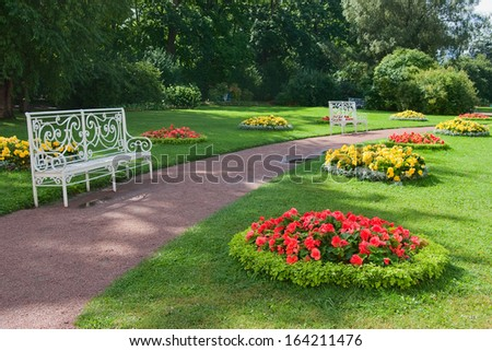 Openwork benches among  flowerbeds in a park. - stock photo
