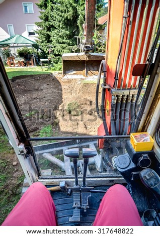 Operating a digger or excavator. Man is driving and operating heavy machinery with shovel in front of him. - stock photo