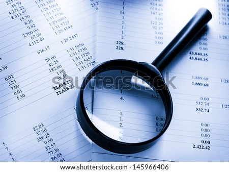 Operating budget and magnifying glass - stock photo