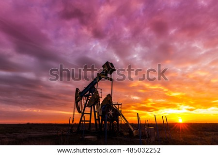 Operating oil and gas well, in remote field, profiled on dramatic sunset