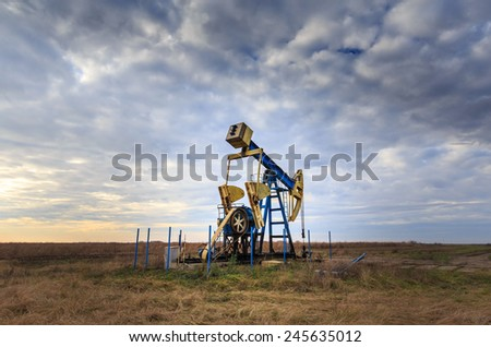 Operating oil and gas well profiled on sunset sky - stock photo