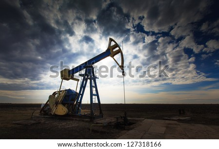 Operating oil well profiled on dramatic cloudy sky - stock photo