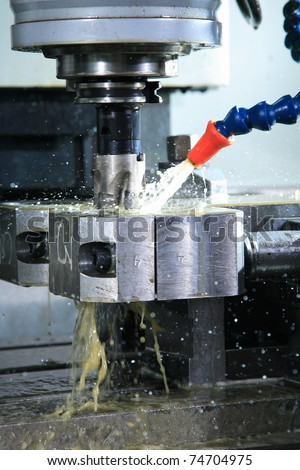 Operation of shaping metal piece machine with metal-working coolant - stock photo