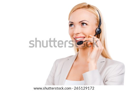 Operator at work. Confident mature customer service representative adjusting her headset and smiling while standing against white background - stock photo
