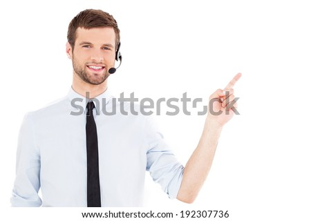 Operator pointing copy space. Handsome young man in formal wear and headset looking at camera and pointing away while standing isolated on white background - stock photo