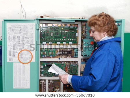 Operator woman-engineer  in machine room (elevator) near electronic cabinet.