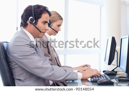 Operators using a computer in a call center - stock photo