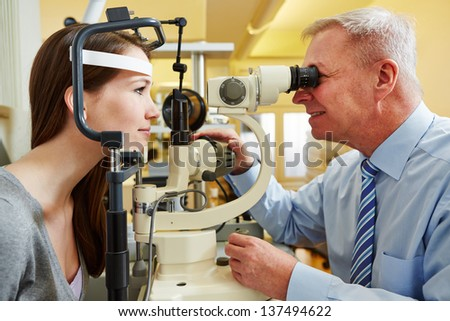 Ophthalmologist examing young woman with a slit lamp - stock photo