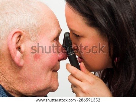 Ophthalmologist examining elderly patient's eye with optical device. - stock photo