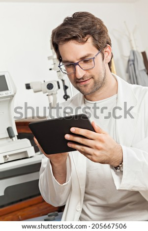 Ophthalmologist In Exam Room Using Digital Tablet