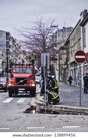 OPORTO, PORTUGAL - DECEMBER 3: Firefighters  supplying water to a fire truck on Boavista district on December 3, 2012 in Oporto, Portugal. - stock photo