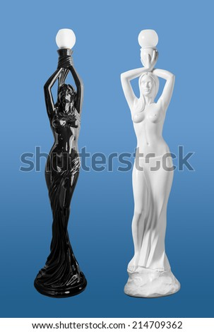 OpposTwo ancient lighting statuettes of women holding bulbs above their heads on blue background. - stock photo