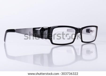 optical black glasses on a light gray background closeup - stock photo