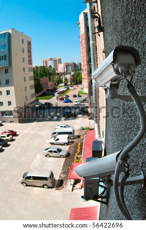 Optical camera on wall of building watching on parking place from top - stock photo
