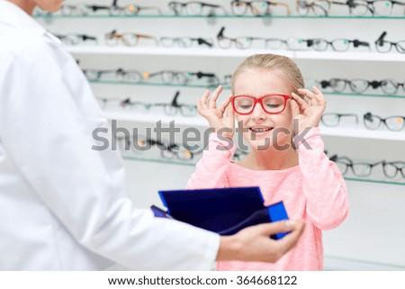 optician and girl choosing glasses at optics store - stock photo