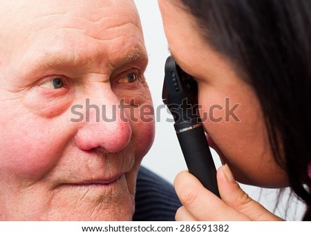 Optician checking elderly patient's cataracts with optical device. - stock photo
